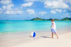 Entzückendes kleines Mädchen, das mit Ball auf Strand spielt Scherzt Sommersport draußen auf karibischer Insel Stockfotografie