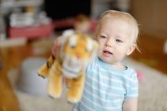 Entzückendes kleines Mädchen, das mit einem Spielzeugtiger spielt Stockfotos