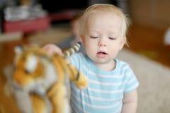 Entzückendes kleines Mädchen, das mit einem Spielzeugtiger spielt Lizenzfreies Stockfoto