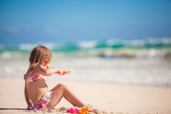 Entzückendes kleines Mädchen, das mit Strandspielwaren spielt Stockfotos