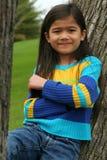 Entzückendes kleines Mädchen, das oben am Baum sich lehnt Lizenzfreies Stockfoto