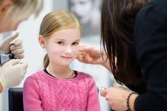 Entzückendes kleines Mädchen, das piercing Prozess des Ohrs in der Schönheitsmitte hat Stockfoto