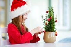Entzückendes kleines Mädchen, das Sankt-Hut verziert kleinen Weihnachtsbaum in einem Topf auf Weihnachtsmorgen trägt Lizenzfreies Stockbild
