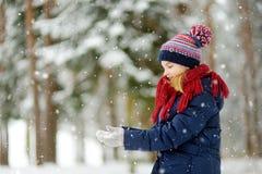 Entzückendes kleines Mädchen, das Spaß im schönen Winterpark hat Nettes Kind, das in einem Schnee spielt stockfotos