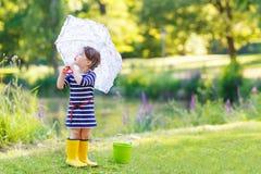 Entzückendes kleines Mädchen in den gelben Regenstiefeln und -regenschirm im Sommer Stockfotos