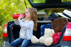 Entzückendes kleines Mädchen drinkig Wasser in einem Auto Stockfoto