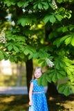 Entzückendes kleines Mädchen durch blühenden Kastanienbaum Lizenzfreie Stockbilder