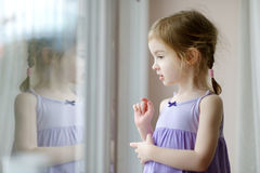 Entzückendes kleines Mädchen durch das Fenster Lizenzfreie Stockfotografie