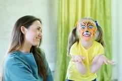 Entzückendes kleines Mädchen gemalt wie der Tiger, der mit Trickzeichner spielt Lizenzfreies Stockfoto