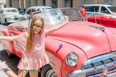 Entzückendes kleines Mädchen im populären Bereich in altem Havana, Kuba Porträt des klassischen amerikanischen Autos der Kinderhi stockbild
