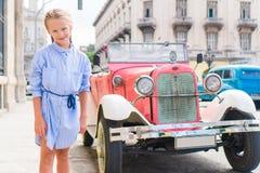 Entzückendes kleines Mädchen im populären Bereich in altem Havana, Kuba Porträt des klassischen amerikanischen Autos der Kinderhi stockfotografie