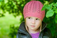 Entzückendes kleines Mädchen im rosafarbenen Hut in einem Park Lizenzfreie Stockfotografie