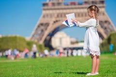 Entzückendes kleines Mädchen mit Karte von Paris-Hintergrund Stockfotos