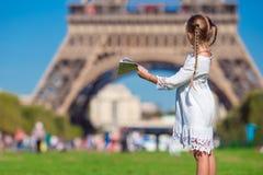 Entzückendes kleines Mädchen mit Karte von Paris-Hintergrund der Eiffelturm Lizenzfreie Stockbilder