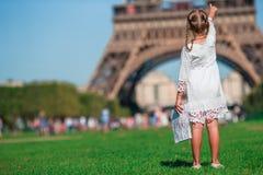 Entzückendes kleines Mädchen mit Karte von Paris-Hintergrund der Eiffelturm Lizenzfreie Stockfotos