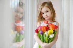 Entzückendes kleines Mädchen mit Tulpen am Fenster Lizenzfreies Stockbild