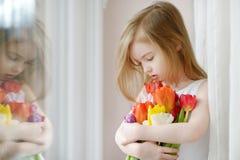 Entzückendes kleines Mädchen mit Tulpen am Fenster Lizenzfreies Stockfoto