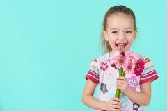 Entzückendes kleines Mädchen mit unverschämtem Lächeln und dem Gesichtsausdruck, die Blumenstrauß von rosa Gerberagänseblümchen h lizenzfreie stockbilder