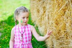 Entzückendes kleines Mädchen nahe einem Heuschober am sonnigen Sommertag stockfotografie