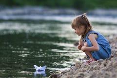 Entzückendes kleines nettes blondes Mädchen im blauen Kleid auf Riverbank pebbl Stockfoto