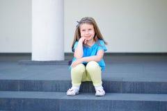 Entzückendes kleines schönes Mädchen, das auf einem Treppenhaus sitzt lizenzfreie stockbilder