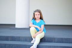 Entzückendes kleines schönes Mädchen, das auf einem Treppenhaus sitzt Stockbilder
