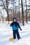 Entzückendes Kleinkind, das mit Schnee draußen spielt Lizenzfreies Stockfoto