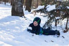 Entzückendes Kleinkind, das mit Schnee spielt Stockbild