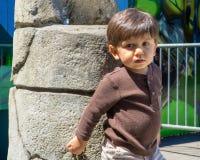 Entzückendes Kleinkind lehnt sich am Brunnen Stockbild