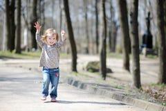 Entzückendes Kleinkindmädchen, das draußen springt Stockfotos