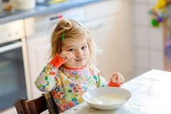 Entzückendes Kleinkindmädchen, das gesundes porrige vom Löffel für nettes glückliches Babykind des Frühstücks im bunten Pyjamasit stockbild