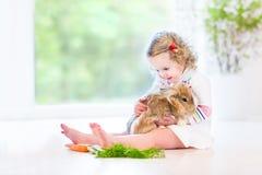 Entzückendes Kleinkindmädchen, das mit einem wirklichen Häschen spielt Lizenzfreie Stockfotografie