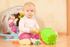 Entzückendes Kleinkindmädchenspiel mit Wanne auf Fußboden Stockbilder