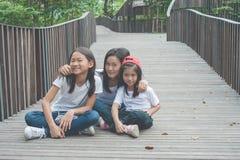 Entzückendes Konzept: Frauen- und Kindersitzen entspannen sich auf hölzernem lächelndem Glück des Gehwegs und des Gefühls im Park stockbild