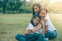 Entzückendes Konzept: Umarmendes und glaubendes lächelndes Glück der Frau und des Kindes im Park stockbild