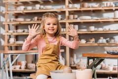 entzückendes lächelndes Kind mit dem Lehm der Töpferscheibe Hände zeigend lizenzfreie stockbilder