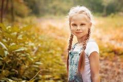 Entzückendes lächelndes kleines blondes Mädchen mit dem umsponnenen Haar Nettes Kind, das Spaß an einem sonnigen Sommertag im Fre Lizenzfreie Stockbilder