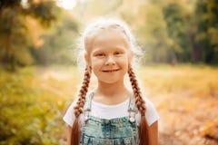 Entzückendes lächelndes kleines blondes Mädchen mit dem umsponnenen Haar Nettes Kind, das Spaß an einem sonnigen Sommertag im Fre Stockfoto