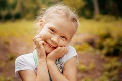 Entzückendes lächelndes kleines blondes Mädchen mit dem umsponnenen Haar Nettes Kind, das Spaß an einem sonnigen Sommertag im Fre Lizenzfreie Stockfotografie