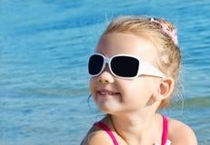 Entzückendes lächelndes kleines Mädchen auf Strandferien lizenzfreie stockbilder