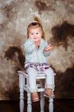 Entzückendes lächelndes kleines Mädchen mit dem blonden Haar, das auf Stuhl sitzt stockbild