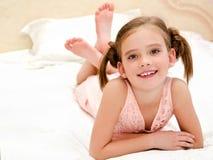 Entzückendes lächelndes kleines Mädchen steht auf einem Bett still Stockbild