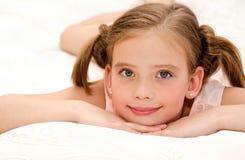 Entzückendes lächelndes kleines Mädchen steht auf einem Bett still Lizenzfreies Stockfoto