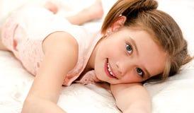 Entzückendes lächelndes kleines Mädchen steht auf einem Bett still Lizenzfreie Stockfotos
