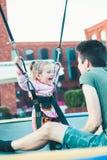 Entzückendes lächelndes Mädchen, das auf Trampoline, Spaß mit ihrem Bruder habend springt stockfoto