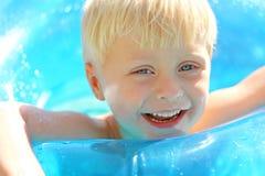 Entzückendes lachendes blondes Kind, das im Swimmingpool spielt Stockfoto