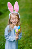Entzückendes lachendes kleines Mädchen mit den rosa Häschenohren und Haltenbündel gemalter Farbe ärgert stockfotografie