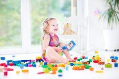 Entzückendes lachendes Kleinkindmädchen mit bunten Blöcken Lizenzfreie Stockbilder