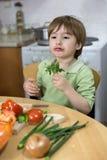 Entzückendes Little Boy, das lustiges Gesicht beim Essen der Petersilie in der Küche macht Lizenzfreie Stockfotografie
