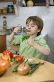 Entzückendes Little Boy, das lustiges Gesicht beim Essen der Petersilie in der Küche macht Lizenzfreies Stockbild